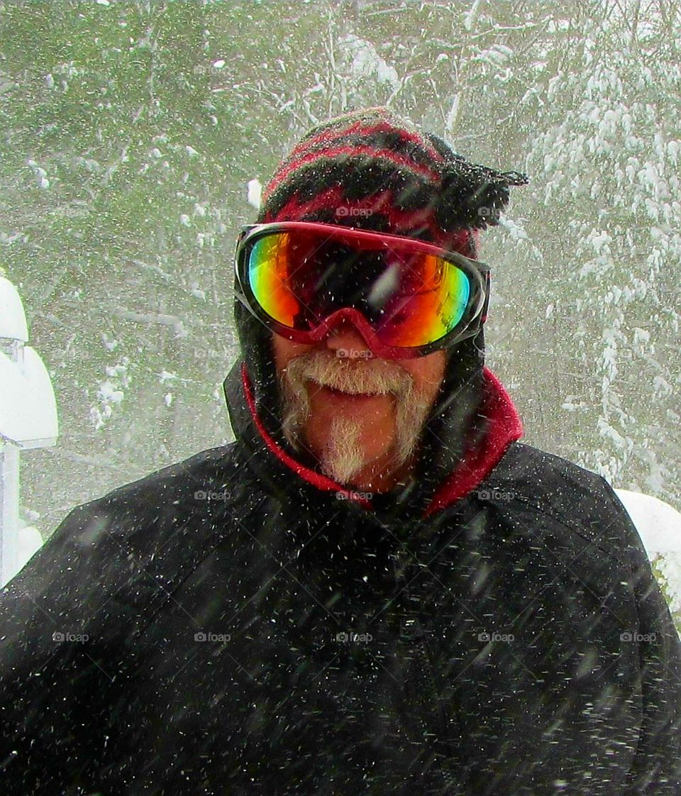Man in snow wearing ski goggles, ski wear, smiling, moustache, as it's snowing out.