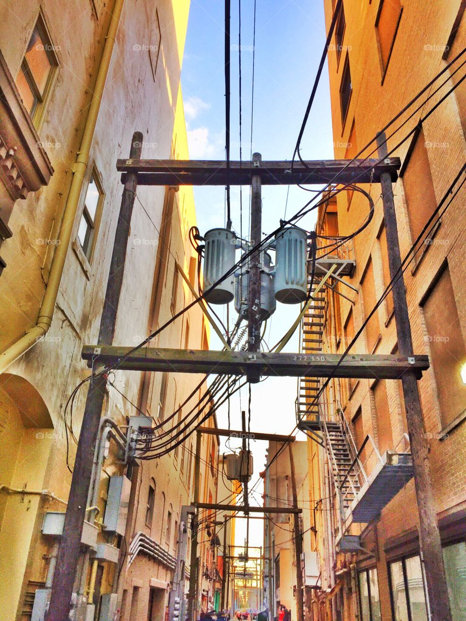 The power grid between buildings in Galveston crest an arched path down the narrow alley way.