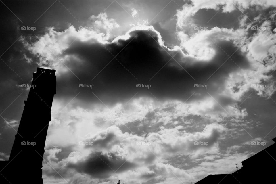 Dramatic black and white capture of a big cloud hovering above a bell tower. Cloudy sky, sinister atmosphere.