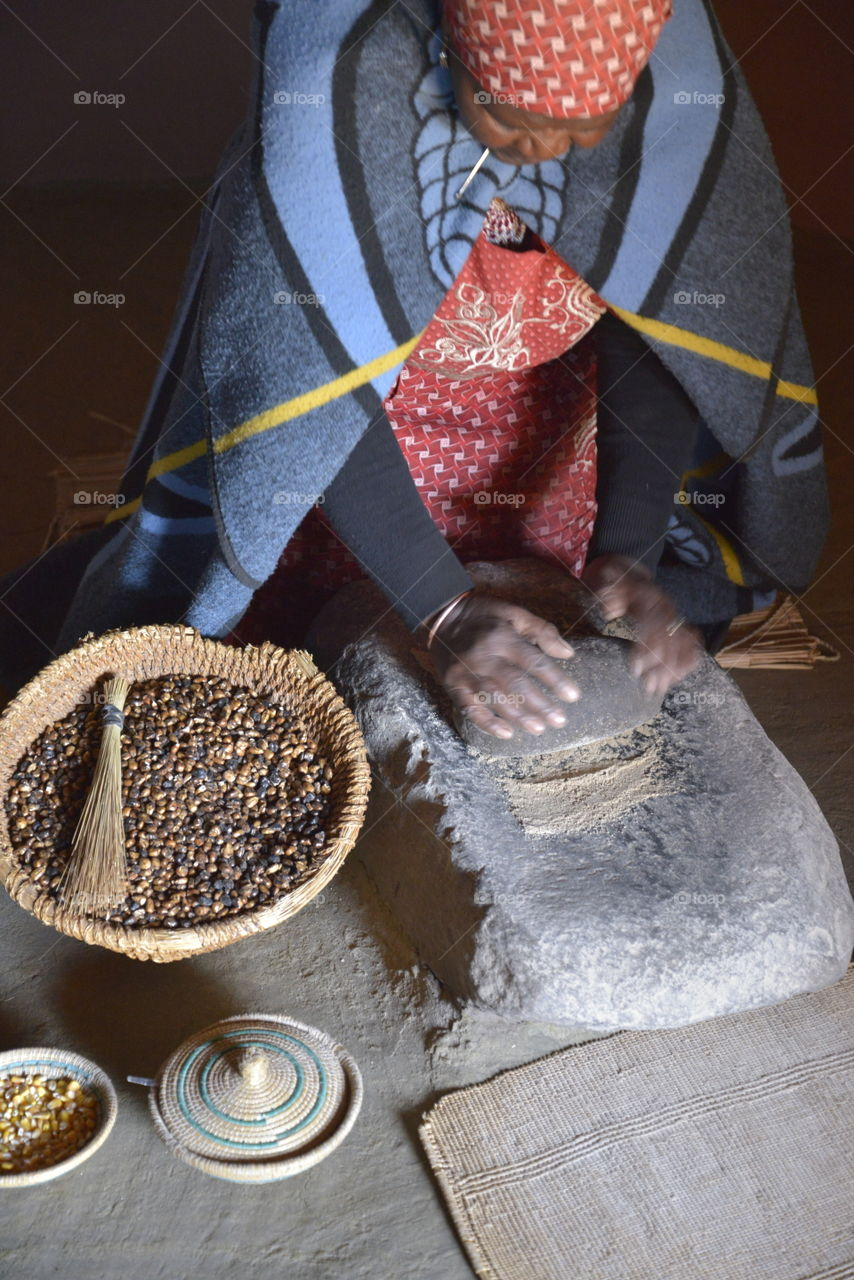 A traditional Basotho gogo (grandmother ) that is showing us how she is crushing Sorghum and corn by using a rock. The produce is used to eat as porridge or used to make a traditional beer.
