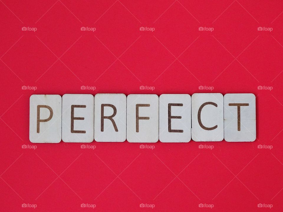 Perfect Spelled out with wooden letters on a red background