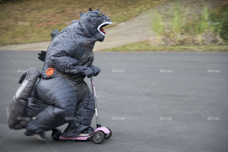 Dinosaur riding a scooter