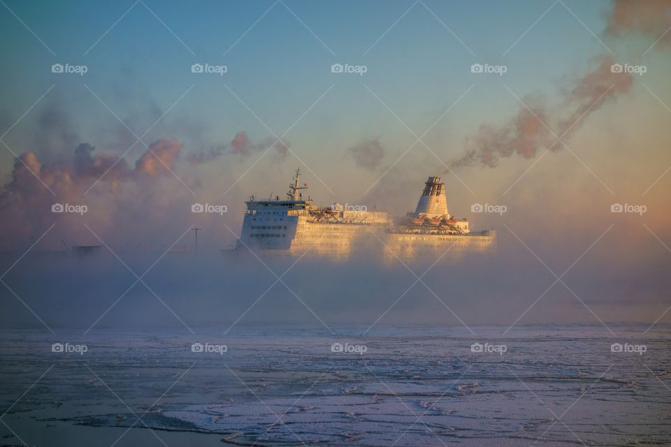 Ferry from Russia approaching Helsinki South harbor in extremely cold winter morning in the middle of thick mist, fog or winter sea smoke that is arising from the rapidly freezing Baltic Sea on 7 January 2016 in Helsinki, Finland.