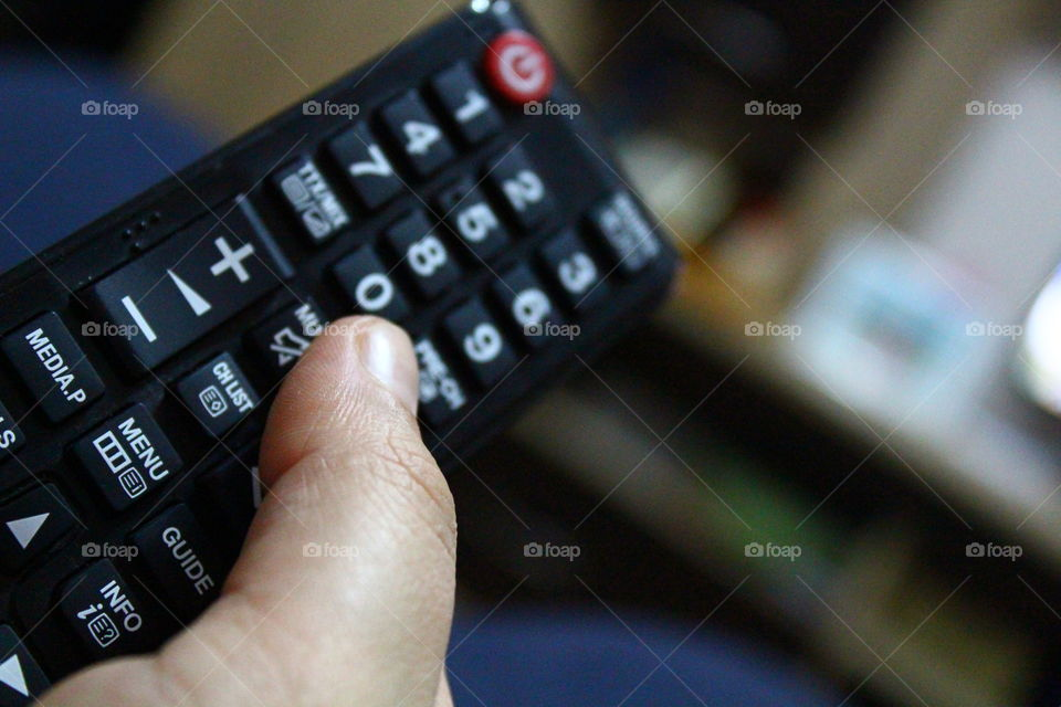 Human hand holding the TV remote focused macro