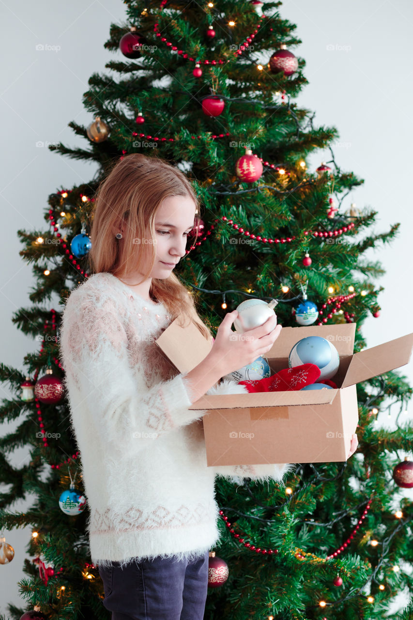 A teenager holding ornament in front of Christmas tree