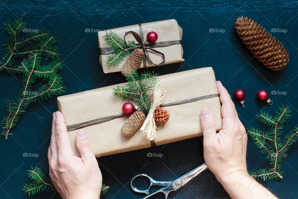 Hands of man decorating Christmas gift box