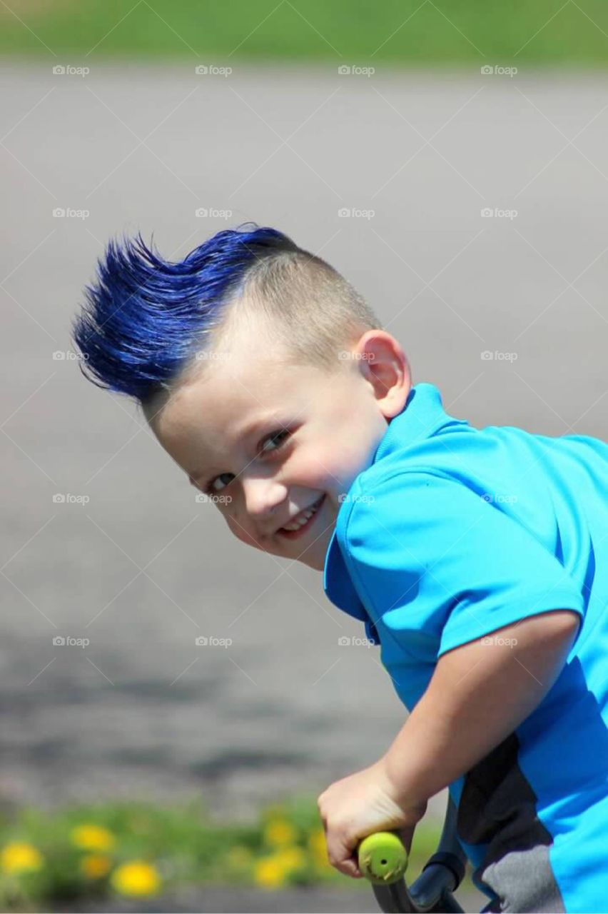 My little boy with a bright blue mohawk with a very mischievous grin on his face.