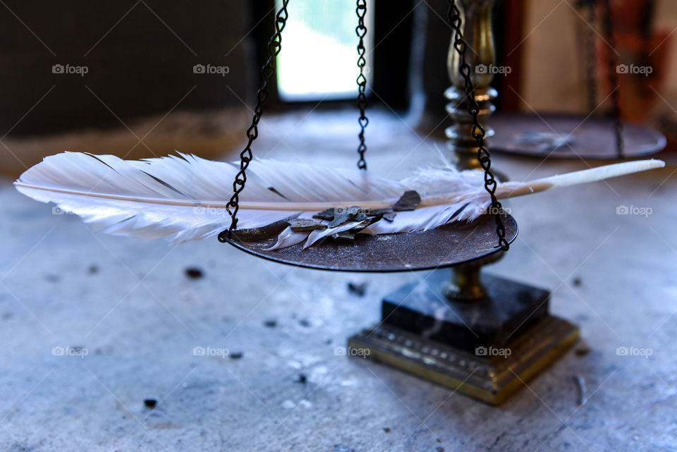 Balance scale with a feather and slivers of stone in front of the natural light from a window