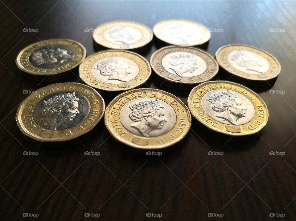 1 pound coins on wood table with copy space at the bottom.
